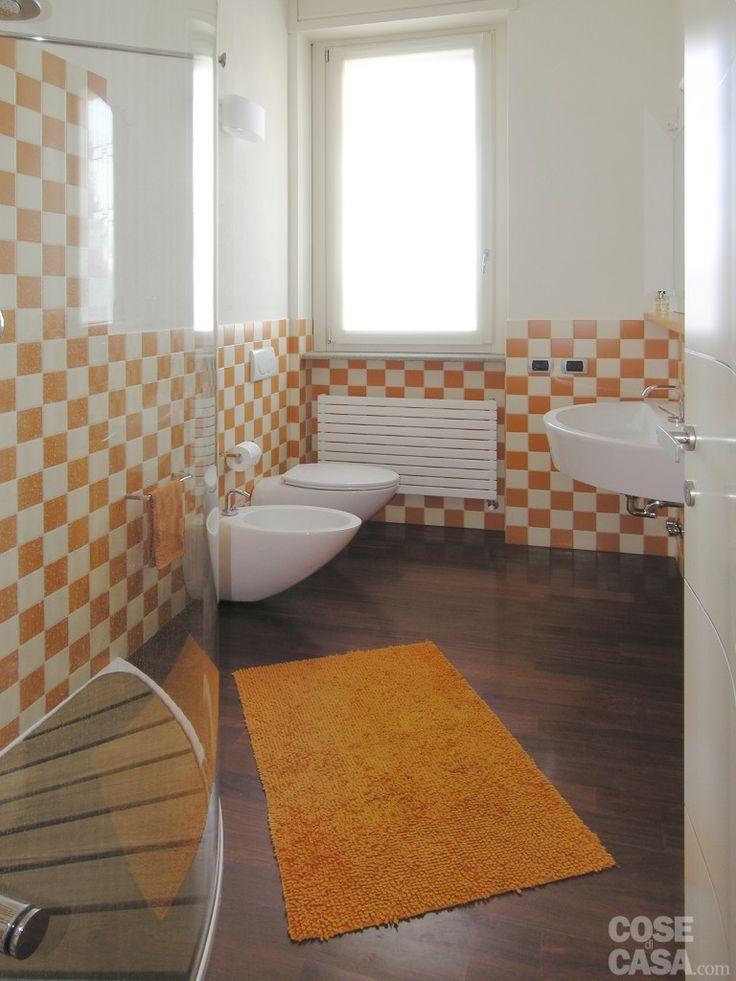 Il bagno ripropone l'alternanza cromatica che caratterizza l'intera abitazione: la fascia bassa delle pareti è rivestita con piastrelle in bicottura bianche e arancio di piccolo formato, posate a scacchiera
