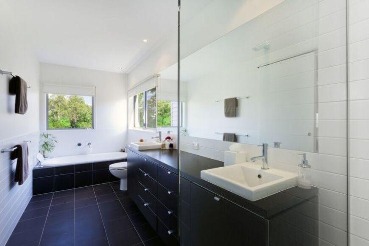Dieses Bad ist in schwarz und weiß gefärbt. Der solide Oberfläche Eitelkeit Zähler ist die gleiche schwarze Farbe wie seine unter Spüle, Schränke und Fliesenböden, während die Wände in weiß sind. Die Waschbecken sind symmetrisch unter in den Zähler montiert.
