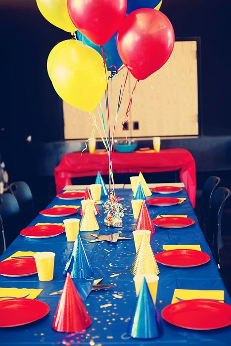 Table setup for party.  Instead use superhero party hats? and superhero weights to weigh down balloon centerpieces.