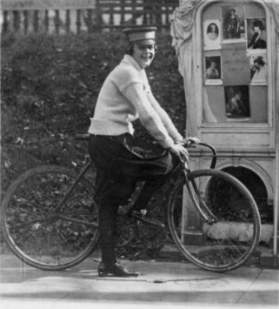 """Woman on bicycle, 1922. Original caption: """"No more messenger boys for the National Woman's Party--from president to messenger all the members of the staff are feminine. This is in accordance with the stipulation of Mrs. Belmont when she donated the National Women's [i.e., Woman's] Party headquarters. Photo of Julia Obear, messenger."""""""