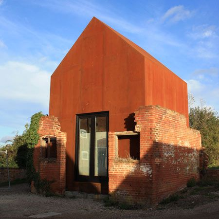 London architects Haworth Tompkins have inserted a Corten steel artist's studio into a ruined Victorian dovecoteinSuffolk, UK. Called The Dovecote Studio, the structure has a pitched rood and occupies the same space as the original building's interior. A skylight in the north side of the roof illuminates the plywood interior, which includes a mezzanine with