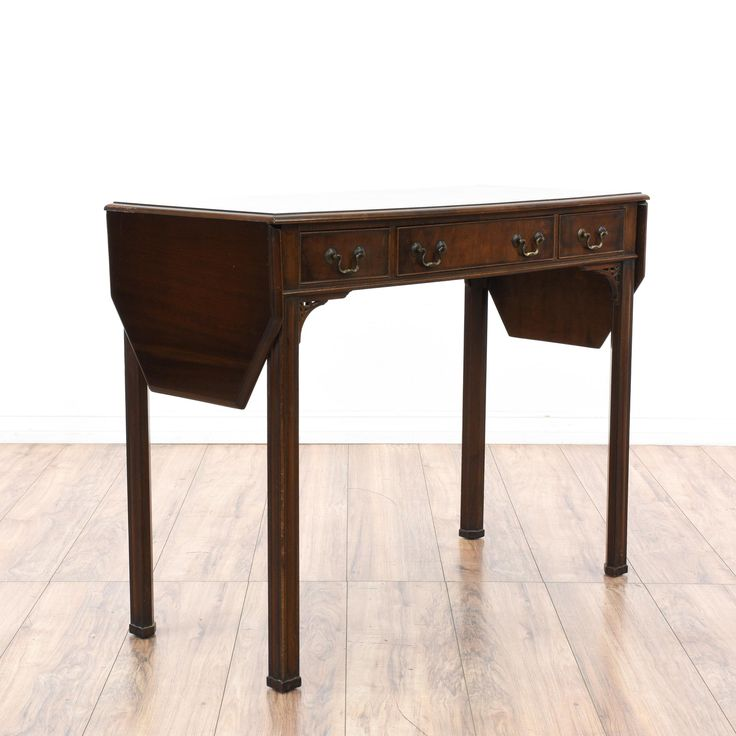 This traditional console table is featured in a solid wood with a dark walnut finish. This sofa table has 3 drawers, side drop leaves and carved corner details. Perfect as a buffet sideboard for storing silverware and drinks! #americantraditional #tables #consoletable #sandiegovintage #vintagefurniture