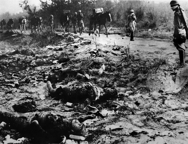On the march toward the siege lines around the town of Myitkyina, Chinese soldiers pass the bodies of dead Japanese troops killed in earlier action against Allied troops.