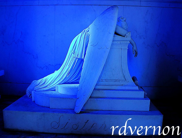 """Blue Angel of Grief    Inside mausoleum of Chapman H. Hyams. Two windows of blue glass, like that in the mausoleum of Queen Louise of Prussia, cast a soft light on a beautiful marble statue of """"Grief,"""" executed in Carara, Italy, from the model of an American sculptor."""