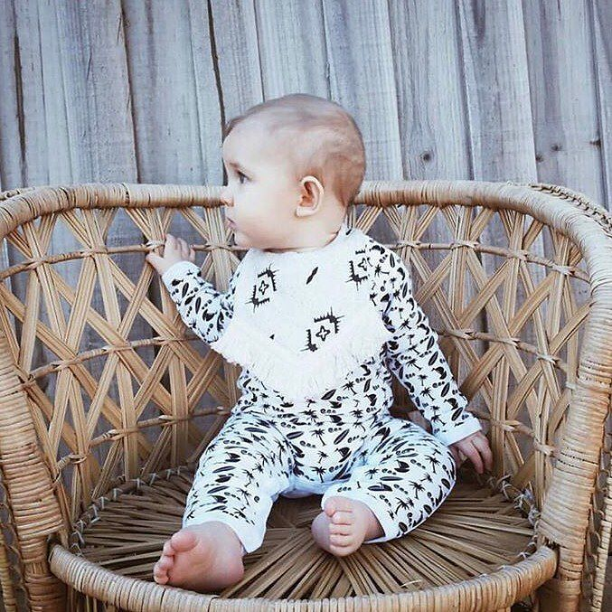 Happy weekend! What have you got planned this wet and windy weekend? . On another note how sweet does this little one look in our ocean breeze romper . @mylittlemikos via @oakie.baby . . . . [image of a female infant sitting on a cane chair and wearing a black and white patterned romper with a black and white fringed bib. She has one hand on the back of the chair and is looking to her right.]