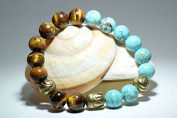 This Unisex Buddha Beaded Bracelet, features 10 mm Tiger Eye, Turquoise Aqua Marine, and a Bronze tone metal Buddha Head and beads separators. #Bracelets #Buddha #Buddhabracelet #Yoga #Bohemian #Boho #Tigereye #Turquoise