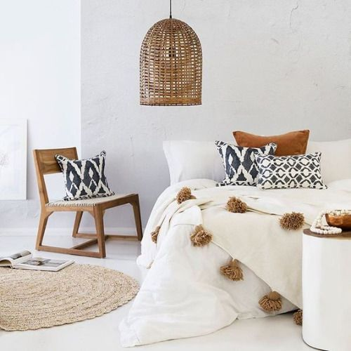 Bohemian bedroom with wicker accents, white bedding with poufs, round area rug