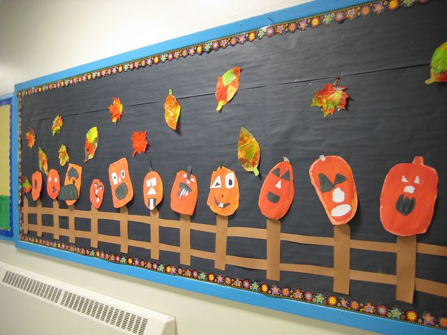 Fall leaves and Jack-O-Lanterns on a fence Halloween bulletin board in Kindergarten.