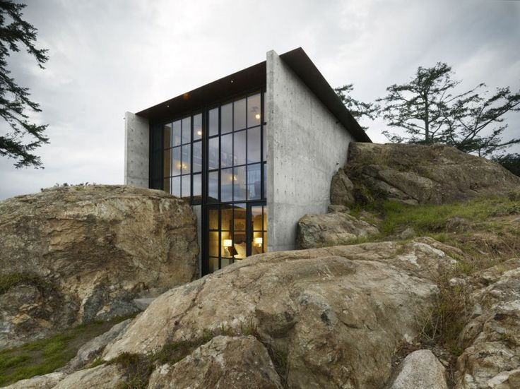 The owner's affection for a stone outcropping on her property and the views from its peak inspired the design of this house. Conceived as a bunker nestled into the rock, the Pierre, the French word for stone, celebrates the materiality of the site. From certain angles, the house – with its rough materials, encompassing stone, green roof and surrounding foliage – almost disappears into nature.    Tom Kundig, Design Principal