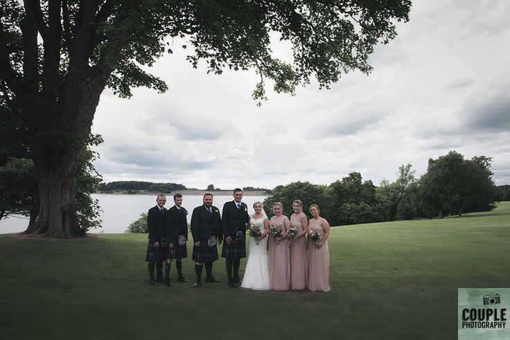 The bridal party in front of the beautiful backdrop of Blessington Lake.  Weddings at Tulfarris Hotel & Golf Resort photographed by Couple Photography.