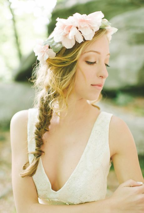 Fishtail Braid with Blush Flower Crown. This bride complements a romantic blush flower crown with a trendy fishtail braid. Balance a bolder style topper with a simple neckline, like this dress's V-neck.