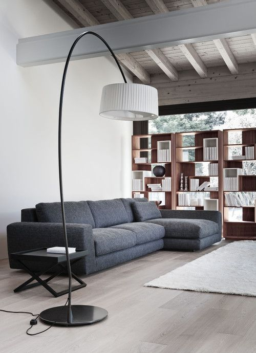 modern utilitarian home. grey sofa. wooden floor. exposed rafters