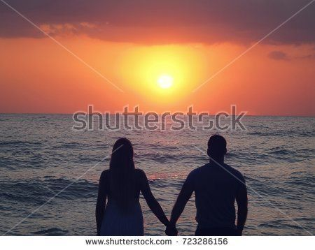 woman and man are standing on the seashore, holding hands. They look at the sunset.