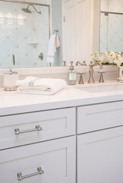 Lovely Bathroom Features White Shaker Vanity Cabinets Adorned With Stain Nickel Pulls Paired Quartz