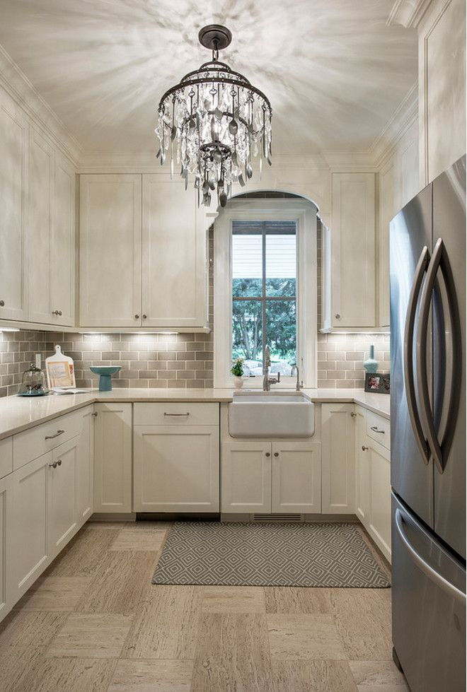 U-shaped kitchen layout. Ivory cabinets with pale gray backsplash.  Alexander Design Group, Inc.
