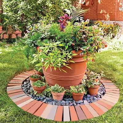 A tidy circle of bricks filled with stones and containers creates a focal point in a section of lawn near the house. The small pots are planted with hens-and-chicks; the large container overflows with a riot of flowers and foliage plants.