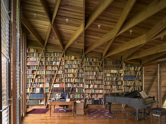 Bookcase wall, reading nook, natural light, and a grand piano in a