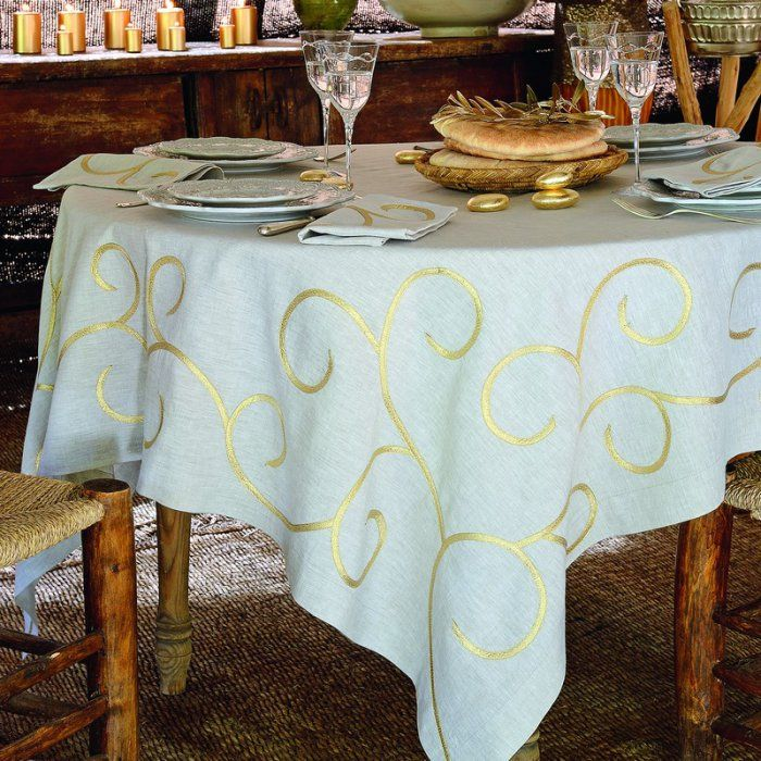 Coudre des rubans dorés sur une nappe et des serviettes