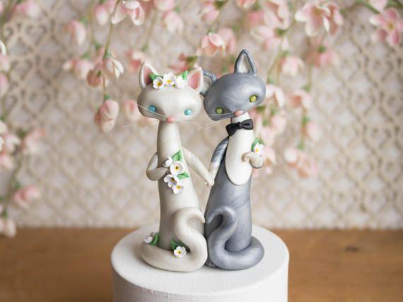 Ce souvenir chat gâteaux de mariage dispose d'une mariée de chat blanc nacrée et un groom de chat Smoking gris orné de fleurs blanches et un noeud papillon noir. Leurs pattes curl en spirales délicates et leur courbe de la queue en forme de coeur.  Je les sculpté à la main avec un mélange personnalisé composé polymère qui a un éclat subtil et persillage. Ils ont long, souples, translucides des moustaches. Leurs yeux sont en nacre et ils se tiennent juste sous 5 pouces hauteur.  Vous recevrez…