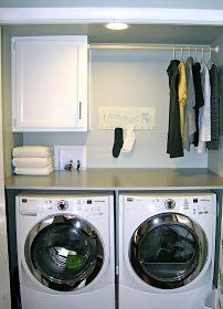 table over washer and dryer with clothes bar and cabinet to hold detergent, etc.