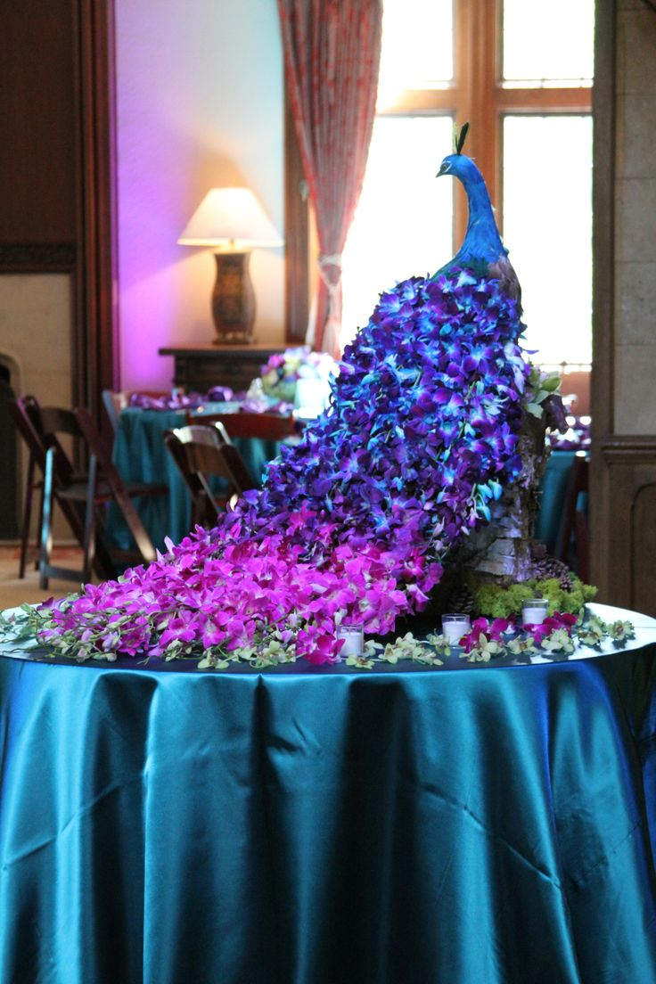 Wedding centerpiece as an entrance piece! The peacock is made completely out of orchids. The peacock colors really complement the dark wood tones o… | The Wow …