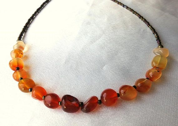 I created this simple, dainty necklace from a spectrum of carnelian pebble beads. Hues of red, orange and creamy white create an ombré arch,