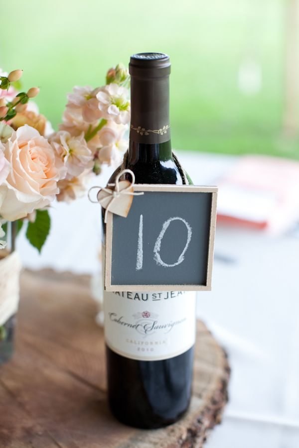 chalkboard table number hanging on a bottle wine #lovethisidea #tablenumber #chalkboards http://www.weddingchicks.com/2013/10/30/peach-and-cream-garden-wedding/