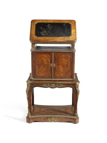 A mid Victorian tulipwood and kingwood marquetry bois de bout floral marquetry folio writing cabinet on stand in the Louis XV/XVI transitional style Applied with gilt bronze mounts, in two parts, the rounded rectangular ratcheted top with moulded edge and tooled leather inset writing surface, above an open tooled leather lined recess and a pair of quarter veneered panelled doors inlaid with riband tied laurel leaves and berries, enclosing a velvet lined interior