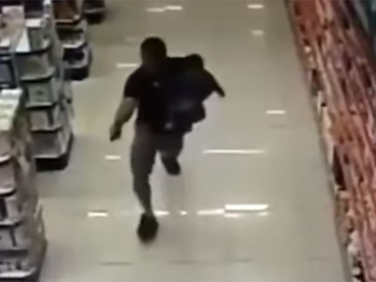 An off-duty military police officer shot dead two armed robbers while holding his child in one arm when the pair tried to hold up a pharmacy, CCTV footage shows.