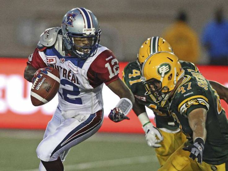 Montreal Alouettes quarterback is pursued by Edmonton Eskimos JC Sherritt, right and Odell Willis during Canadian Football League game in Montreal Thursday August 13, 2015. Cato was sacked on the play.