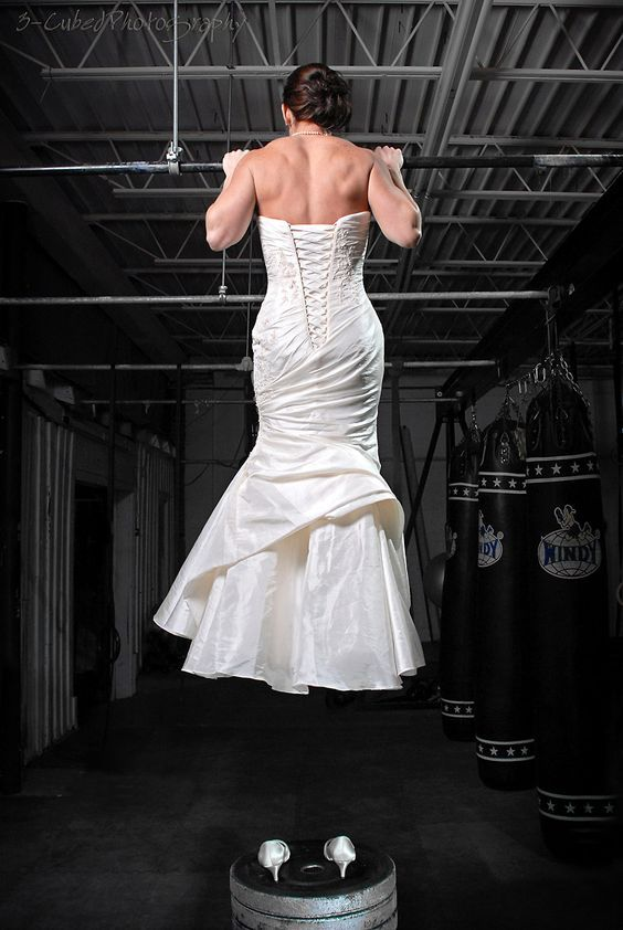 Pictured: Someone unfit for portrayal in a video game. - (Light skinned woman with a very visibly muscular back and arms doing chin ups while wearing a wedding dress)