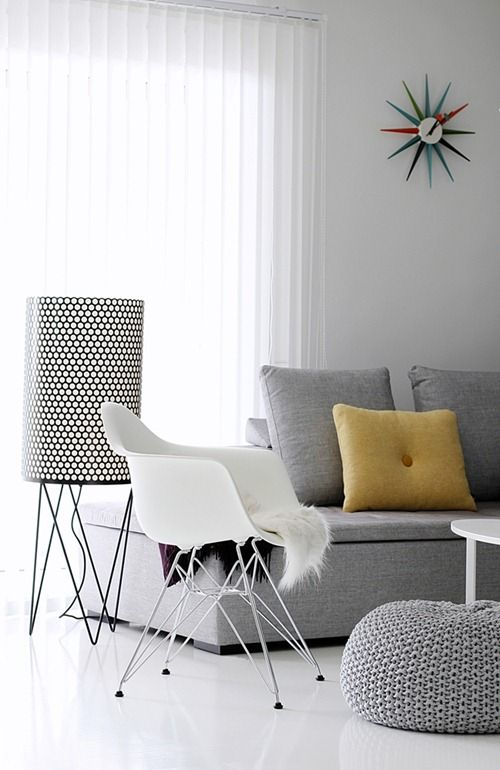 Mustard coloured cushion adds a nice contrast to the grey and white furniture. Gubi Floor Lamp. Eames Rocker. Homemade pouffe.