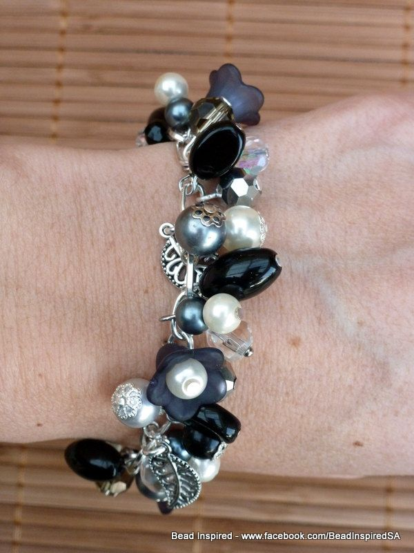 This pretty Black and Cream Flower Garden Bracelet has a gorgeous mix of beads, Lucite flowers (that look like black pansy flowers) and filigree silver plated leaf charms attached to a silver plated cable chain. This pretty charm bracelet has a gorgeous mix of beads, Lucite flowers and filigree silver plated leaf charms attached to a silver plated cable chain. I have used glass (including pearl), crystal and metallic beads. The beads are in a mixture of shapes – round, round faceted, oval…