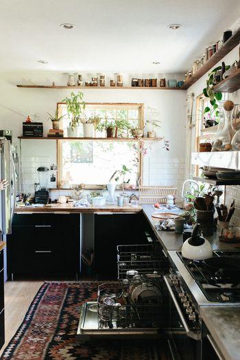 シックな黒と白のコントラストがお洒落なキッチン。ナチュラルな木目や観葉植物のグリーンがアクセント。