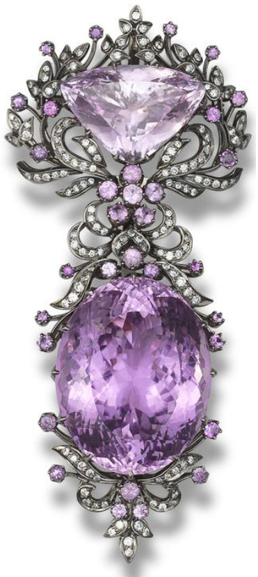 A kunzite and diamond brooch. Designed as a detachable brooch, which can be worn as two separate pendants, set with an oval mixed-cut and a triangular mixed-cut kunzite, within a foliate surround set...