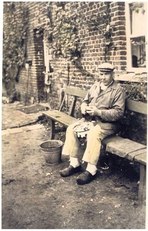 Het schillen van aardappelen door Jacobus Beijk, bijgenaamd Coop van de Hoort, voor zijn ouderlijk huis: het eerste huis gebouwd te Budel Dorplein in 1873  Heijlighen, H. (fotograaf) - 1928 - 1932