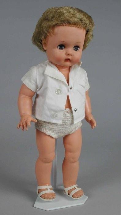 Pop, meisje van kunststof met blauwe slaapogen en kort blond haar, gebreide onderbroek en wit katoenen hemdjasje en witte plastic schoenen