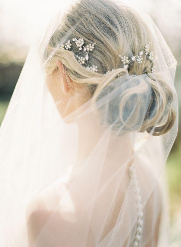 Sweet little hair accessories stand out through a sheer veil // via Colin Cowie Weddings.