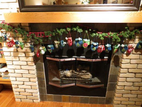 Advent mittens on Fireplace. Each mitten has a piece of the Playmobil Nativity scene