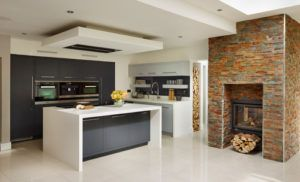 A glass-covered fireplace is embedded into a brick chimney breast wall providing warmth in this modern-styled kitchen.