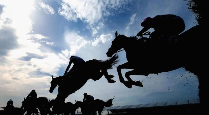 Silhouette of Grand National runners jumping fences at Aintree, Liverpool. Photo: Alex Livesey/Getty Images