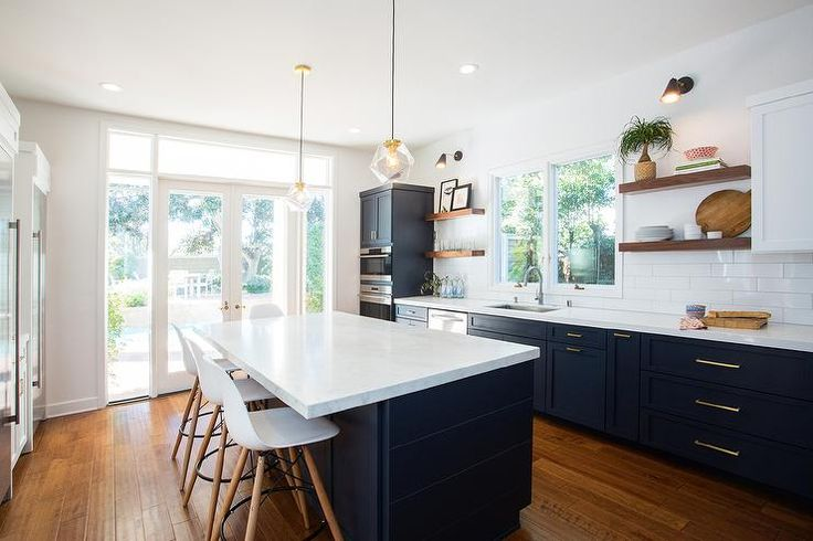 Fabulous kitchen features navy blue shaker cabinets adorned with aged brass pulls paired with white quartz countertops that resemble marble and a white stacked tile backsplash.