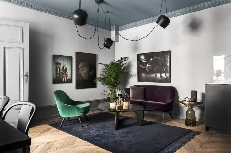 This unique contemporary interior features FLOS AIM pendant lights along with a forest green armchair, a dark purple sofa and an array of wall art.