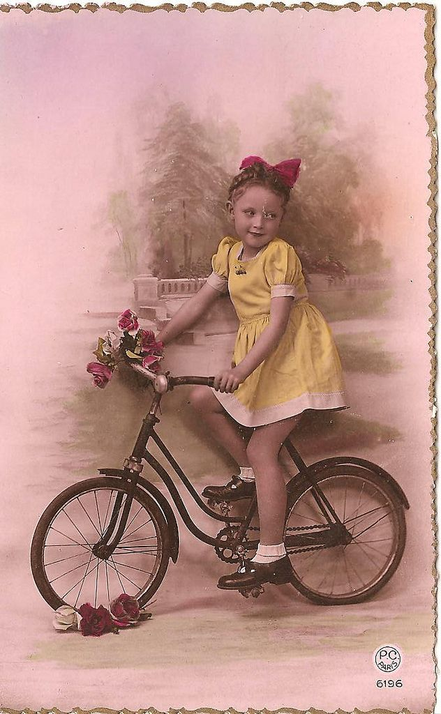 vintage photo of girl in yellow dress on a tiny bicycle