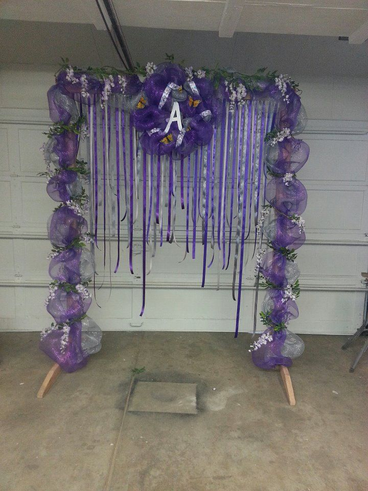 Custom homemade wedding arch. Created using 2x4's to make a sturdy base. Then decorated with deco mesh and flowered garland. A custom made wreath hangs from the top and different lengths of grey and purple ribbon hang to make a beautiful back drop. For the ceremony we also added small glass cups with water beads and blue orchids that hung from some of the ribbon.