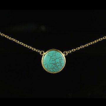 Simple Circle Necklace displays a stunning turquoise stone and hangs from a gold-plated bronze chain.