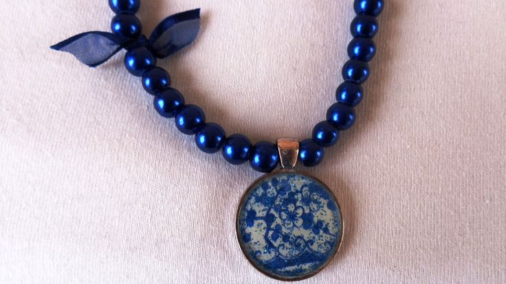 A blue porcelain decoupage necklace, silver pendant, blue pearls, silver chain, silver beads, napkin, liquid glass.  https://www.etsy.com/listing/207488077/a-blue-porcelain-decoupage-necklace?ref=shop_home_active_1