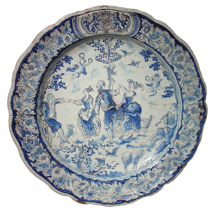 """Nevers - French Faience Platter. Decorated with a Festive Outdoor Gathering with People Dancing and Musicians Playing. There are Lambs, a Dog, Birds, and Cherubs Holding Wreaths, Joyfully Floating above.  Nevers, France. Circa 18th Century. 19-3/4"""" (50cm)."""
