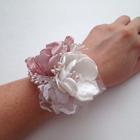 Este precio es para un ramillete.  Flores de tela hechas a mano, en tonos crema y rosa polvoriento. Terminó con adornos y encajes de plata.