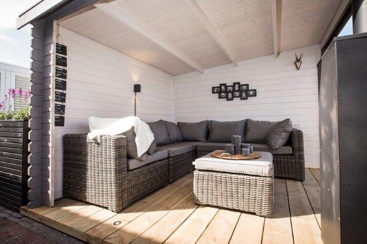 Het tuinhuis met overkapping is gebeitst in aarde tinten. De vloer is gemaakt van grenene hout met daarop donker grijze all weather loungeset en een terras haard met schoorsteen. De bloembak is op maat gemaakt van Douglas 'rhombusprofiel'. De antraciete 60 x 60 cm. betontegel Granitops is kleurvast.